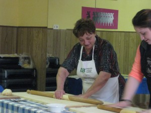 A neighbor helps out at the farm as well - she is rolling out the pasta here.